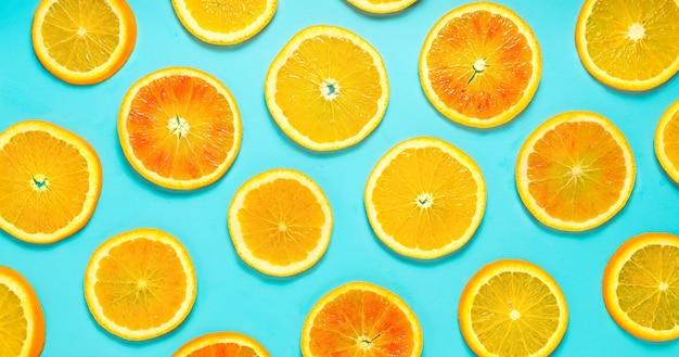 Fette d'arancia fresche modellate su sfondo turchese. direttamente sopra.