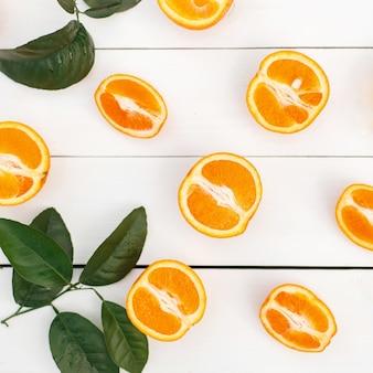 Arancia fresca con foglie su un tavolo di legno bianco