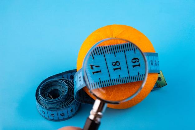 Arancia fresca con una lente d'ingrandimento su un nastro di misurazione blu - dieta, fitness, stile di vita, concetto sano e vegetariano