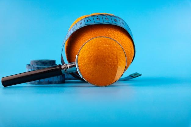 Arancia fresca con una lente d'ingrandimento su un nastro di misurazione blu