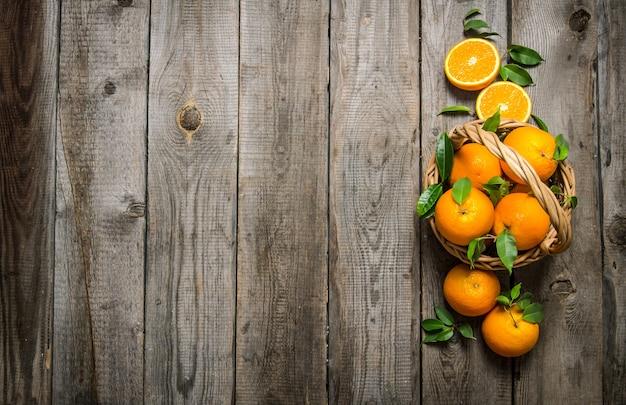 Arance fresche nel cestino con foglie sulla tavola di legno. vista dall'alto