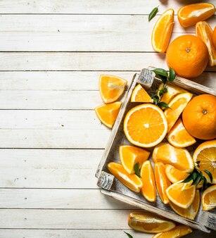 Arance fresche in una scatola. su un tavolo di legno bianco.