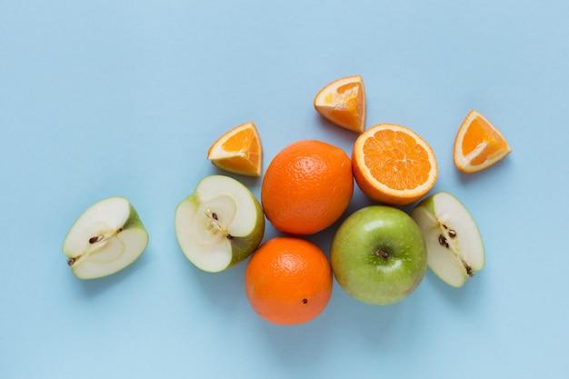 Arance fresche e mele verdi sulla superficie blu