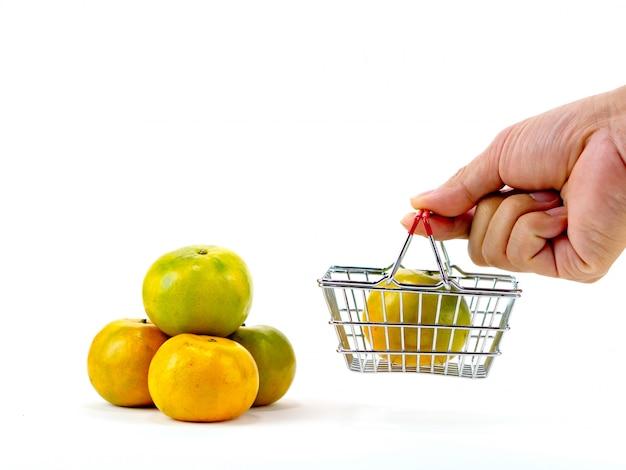Le arance fresche e carrello, concetto di acquisto di cesto con sfondo bianco