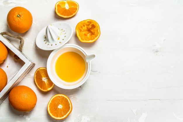 Arance fresche in vassoio e spremiagrumi. su sfondo bianco rustico