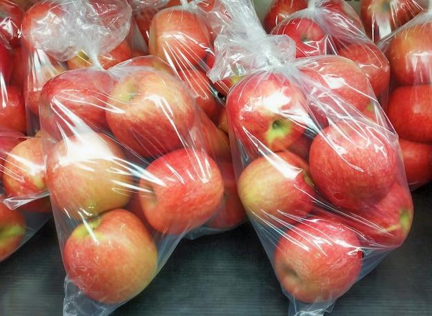 Le mele biologiche fresche sono confezionate in sacchetti di plastica pronte per la vendita nei supermercati.