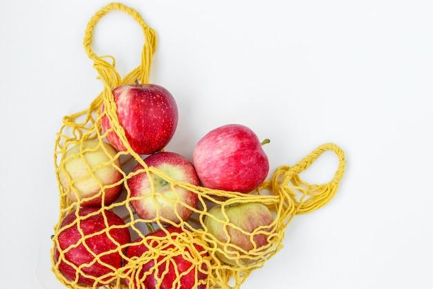 Mele organiche fresche in un sacchetto tessile giallo di acquisto su fondo bianco, orientamento orizzontale, concetto di spreco zero, spazio della copia