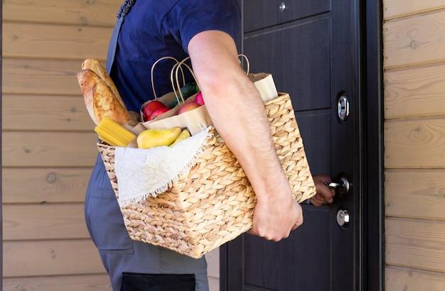 Pane biologico fresco, verdure, verdure e frutta, cereali e pasta in un cesto di vimini nelle mani di un corriere in bicicletta. consegna o donazione ecologica della bici del concetto di cibo agricolo ecologico.