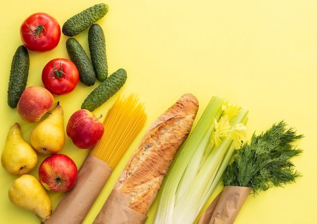 Pane biologico fresco, verdure, verdure e frutta, cereali e pasta su un tavolo giallo. concetto di cibo di fattoria ecologica. vista dall'alto. lay piatto