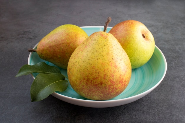 Pera bio coltivata biologica fresca con foglie sul piatto