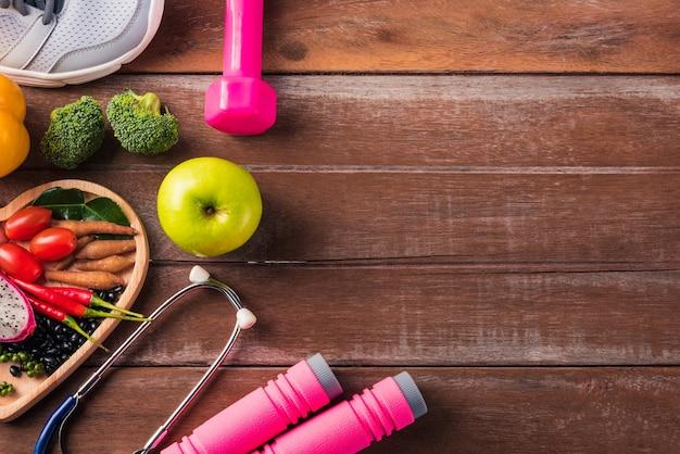 Frutta e verdura biologica fresca in piatto cuore, scarpe, attrezzature sportive e stetoscopio medico