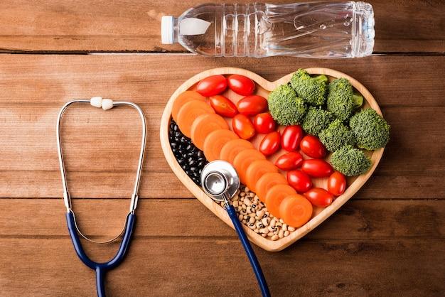 Frutta e verdura biologica fresca in stetoscopio medico con piastra a cuore e bottiglie d'acqua in plastica