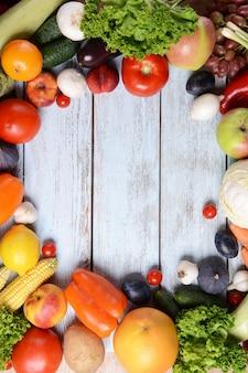 Frutta e verdura organiche fresche su fondo di legno