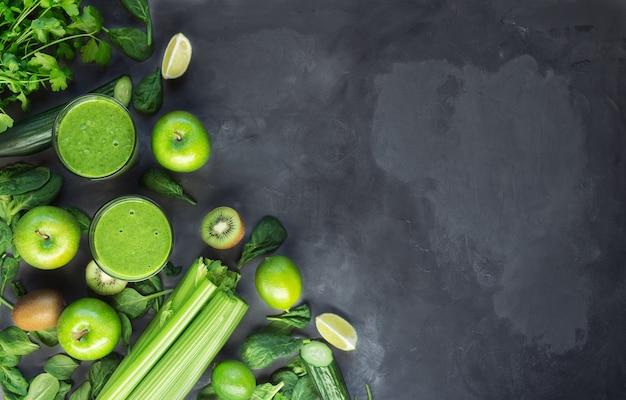 Frullato verde biologico fresco con ingredienti su sfondo grigio cemento. vista dall'alto. copiare l'area dello spazio.
