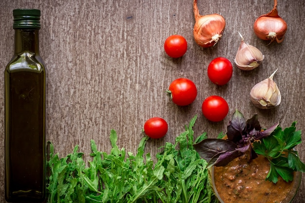 Ingredienti biologici freschi per la preparazione di salsa di spinaci pomodori germogli basilico olio d'oliva su sfondo rustico...