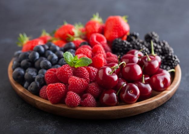 Le bacche estive organiche fresche si mescolano in vassoio di legno rotondo sul fondo nero del tavolo da cucina. lamponi, fragole, mirtilli, more e ciliegie. vista dall'alto