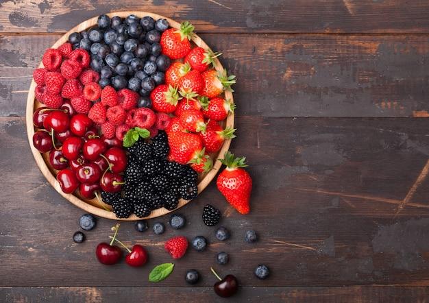 Le bacche estive organiche fresche si mescolano in vassoio di legno rotondo sul fondo di legno scuro della tavola. lamponi, fragole, mirtilli, more e ciliegie. vista dall'alto