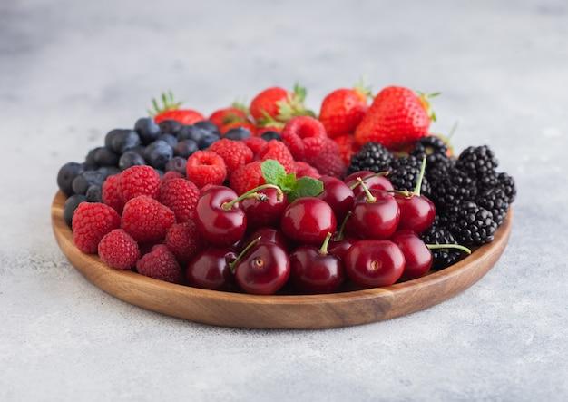 Le bacche estive organiche fresche si mescolano in vassoio di legno rotondo sul fondo leggero del tavolo da cucina. lamponi, fragole, mirtilli, more e ciliegie. vista dall'alto