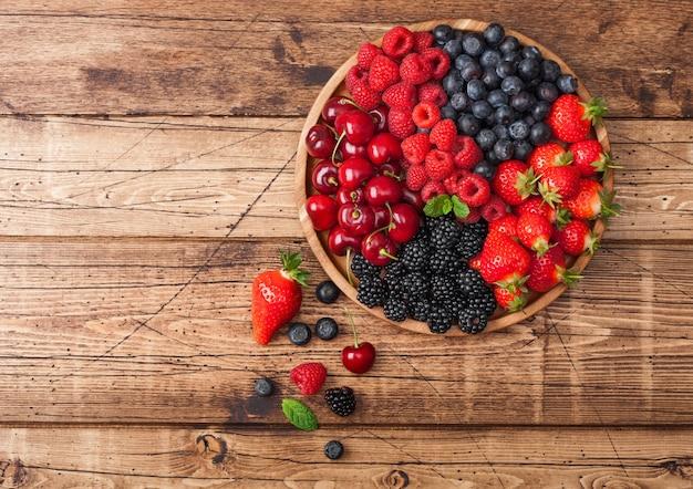 Le bacche estive organiche fresche si mescolano in vassoio di legno rotondo sul fondo di legno chiaro della tavola. lamponi, fragole, mirtilli, more e ciliegie. vista dall'alto
