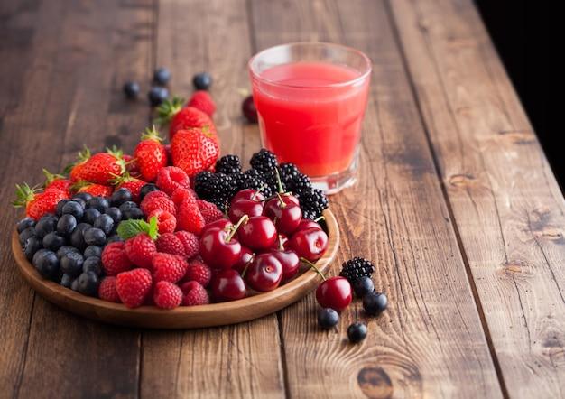 Fresche bacche estive organiche si mescolano in un vassoio di legno rotondo con un bicchiere di succo su un tavolo di legno