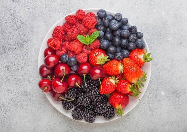 Le bacche estive organiche fresche si mescolano in piatto bianco sul fondo leggero del tavolo da cucina. lamponi, fragole, mirtilli, more e ciliegie. vista dall'alto