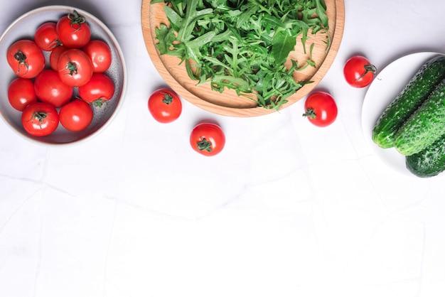 Verdure organiche fresche e vegetazione per una cucina sana su sfondo di pietra chiara vista dall'alto