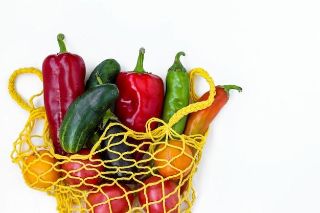 Verdure biologiche fresche in una borsa a rete gialla, formato orizzontale, concetto di rifiuti zero