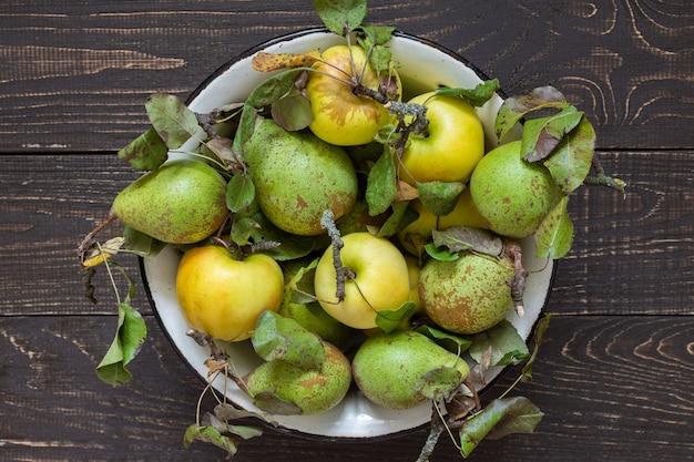 Mele gialle organiche fresche e pere verdi in una ciotola di ferro su un fondo di legno marrone naturale
