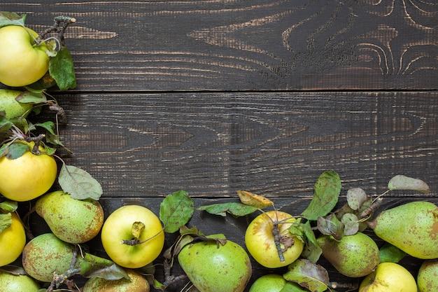 Mele gialle organiche fresche e pere verdi con foglie su un fondo di legno marrone naturale