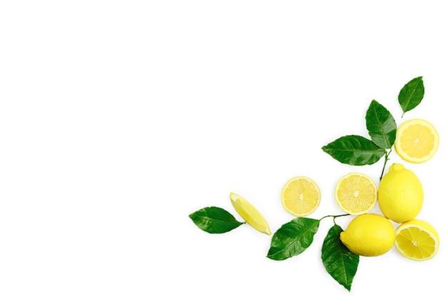 Frutta fresca organica giallo limone lime con fette e foglie verdi isolati su priorità bassa bianca. vista dall'alto. lay piatto. copyspace per il testo.