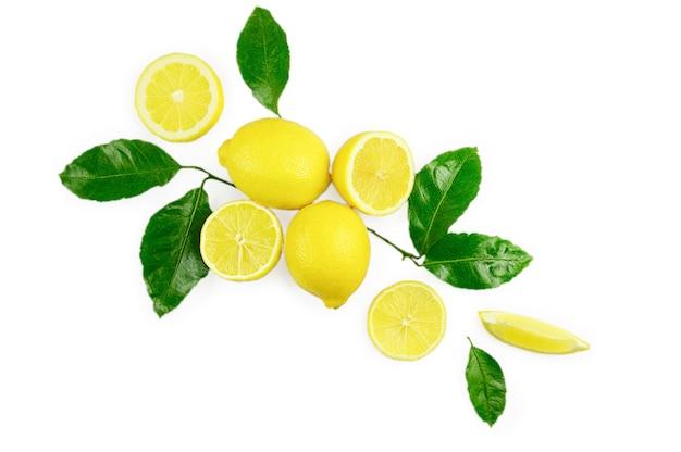 Frutta fresca organica giallo limone lime con fette e foglie verdi isolati su priorità bassa bianca. vista dall'alto. lay piatto.