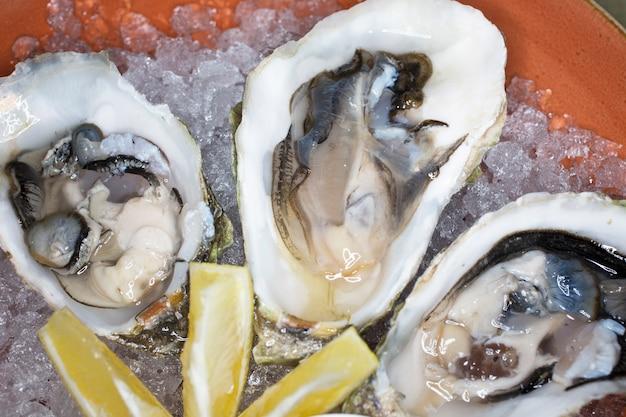 Ostriche fresche in una ciotola con ghiaccio limone e salsa di crostacei nel ristorante una lussuosa cena sana