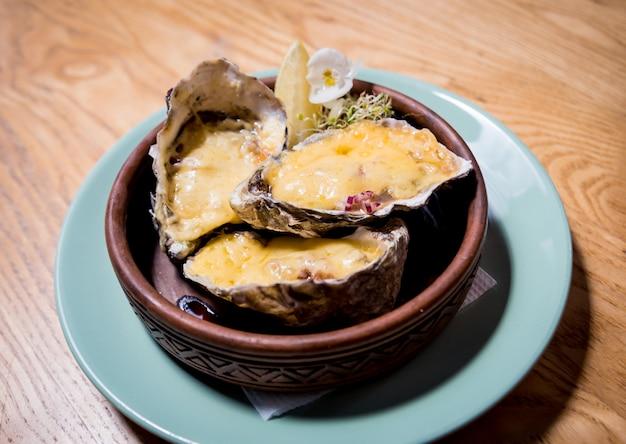Ostriche fresche sotto formaggio su un piatto con ghiaccio e fiori. ristorante