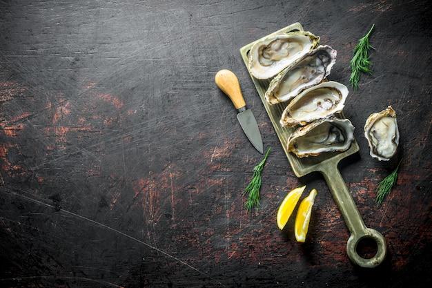 Ostriche fresche sul tagliere con fette di limone sul tavolo di legno scuro