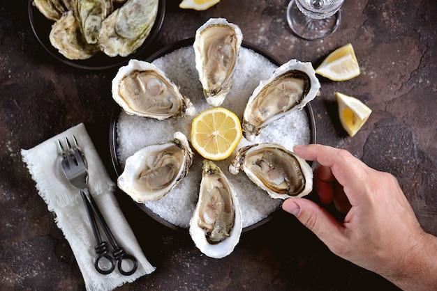 Ostriche fresche su un grande sale marino al limone. cibo sano, cibo gourmet, cibo da ristorante. vista dall'alto.