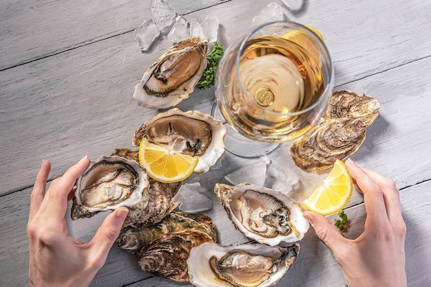 Ostriche fresche con limone, ghiaccio e vino bianco
