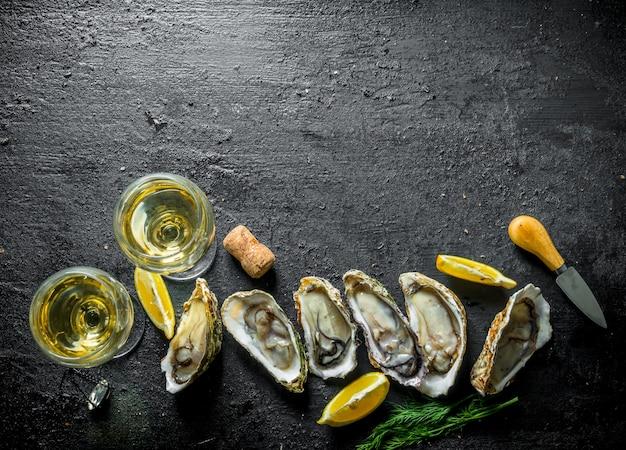 Ostriche fresche al vino bianco. su sfondo nero rustico