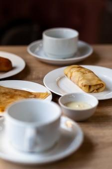 Frittelle fresche con ripieno sul tavolo accanto a tazze bianche per caffè o tè per colazione. frittelle per un dolce dessert dopo pranzo in un accogliente caffè.