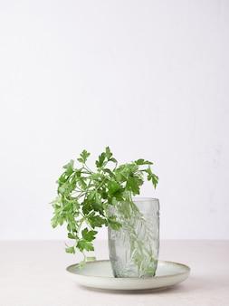 Mazzo di prezzemolo fresco con gocce d'acqua sulle foglie in un bicchiere sul piatto.