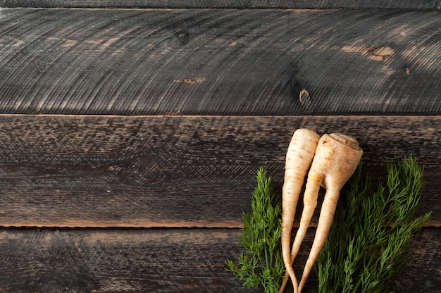 Radice e pastinache fresche di prezzemolo su fondo di legno
