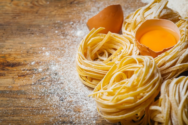 Alimenti per pasta fresca. pasta italiana fatta in casa cotta su un tavolo di legno in stile rustico decorato con uova e farina. Foto Premium