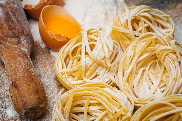 Alimenti per pasta fresca. pasta italiana fatta in casa cotta su un tavolo di legno in stile rustico decorato con uova e farina.