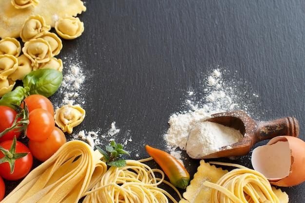Pasta fresca e ingredienti su un bordo scuro con copia spazio