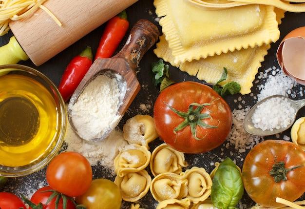 Pasta fresca e ingredienti su una tavola scura