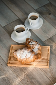 Croissant di pasticceria fresca con cioccolato su una tavola di legno e due tazze di caffè nero. colazione romantica