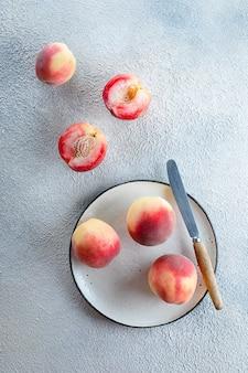 Pesche fresche sul piatto con coltello