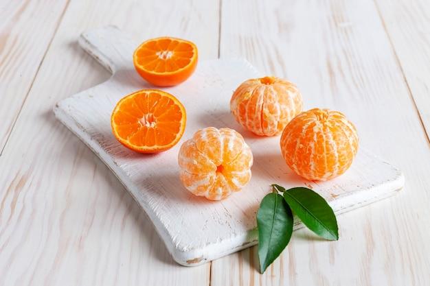 Mandarini sbucciati freschi su fondo bianco