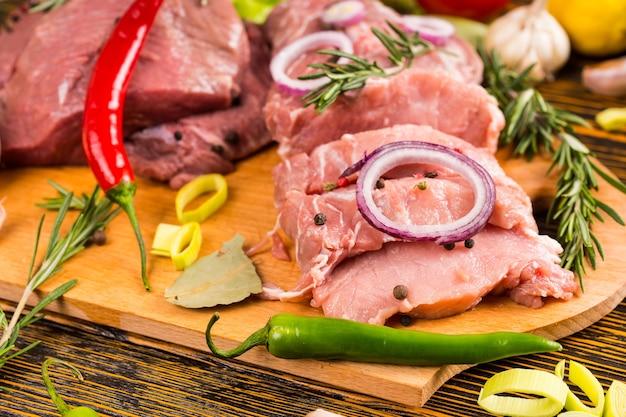 Peperoni freschi e cipolle di vario tipo e colore con pezzi di carne cruda sul tagliere accanto a rametti di rosmarino, lattuga, pomodoro, funghi e aglio