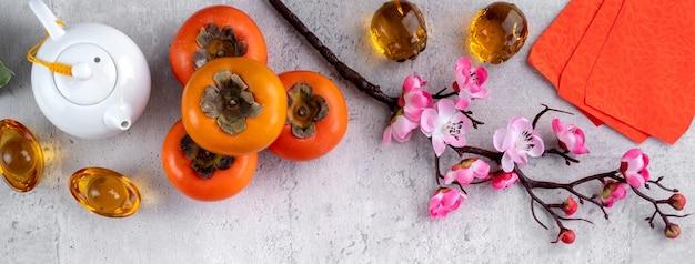 Cachi freschi su sfondo grigio del tavolo per il disegno della frutta del capodanno cinese, le parole sulla moneta d'oro indicano il nome della dinastia che ha fatto.