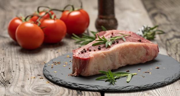 Pezzo di manzo fresco, bistecca di controfiletto su un bordo nero con spezie, da vicino